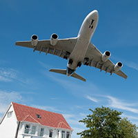 Airplane flying over house